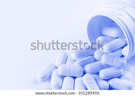 Pills spilling from container - stock photo