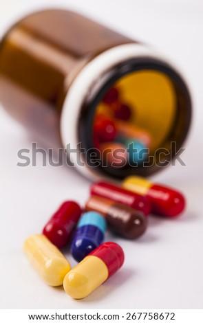 Pills spilling out of prescription bottle - stock photo