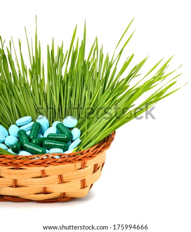 Pills, tablets and wheat grass in the basket isolated on white - stock photo