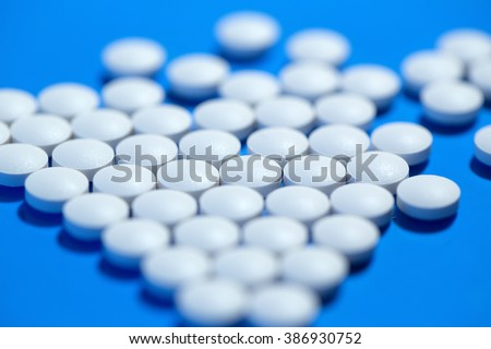 Pills. White medical pills on blue background. - stock photo