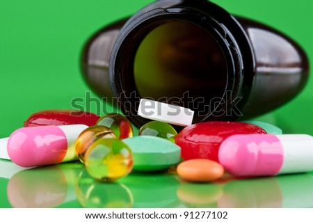 pills with bottle on a green background - stock photo