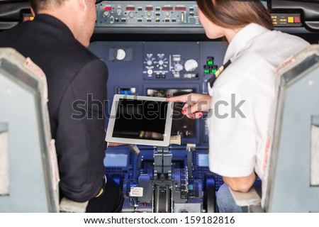 Pilot and Copilot Checking Flight Information on Digital Tablet - stock photo