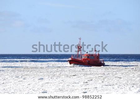 Pilot boat sailing through ice near port of Riga in winter - stock photo