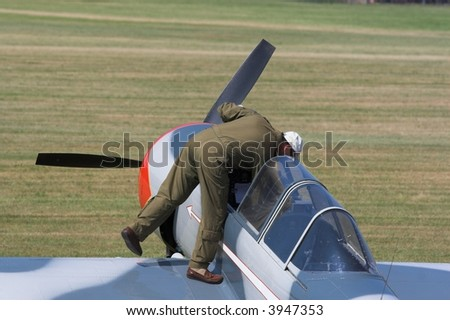 Pilot entering plane - stock photo