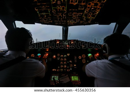 Pilot in airplane cockpit after sunset - stock photo