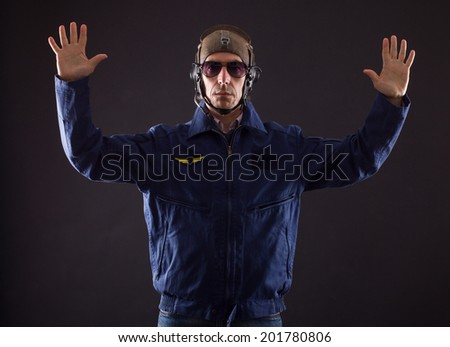 Pilot in military uniform on a black background. - stock photo