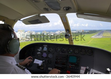 Pilot is getting ready for landing overlooking the city, ocean, beach and landing strip on the background. - stock photo
