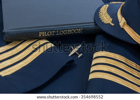 Pilot logbook with Captain 4 gold stripes on sleeves with Captain hat and Dash 7 pin.