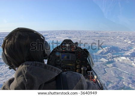 Pilot of a small airplane flies over ice shields of the Arctic Ocean above ice and slow on the background of blue sky - stock photo
