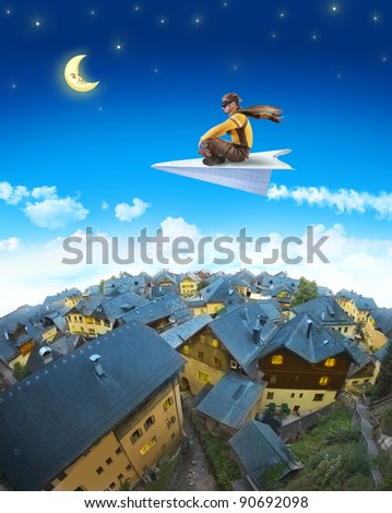 Pilot riding the paper plane above sleepy town in the moonlight - stock photo