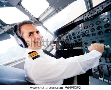 Pilot sitting in an airplane cabin flying - stock photo