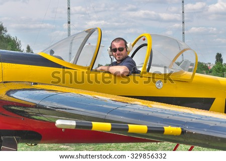 Pilot sitting in the cockpit of a light aerobatic plane
