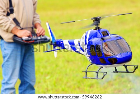 Piloting Radio controlled helicopter (scale-model 1:24 scale) with remote control. Teleobjective shot with shallow DOF. - stock photo