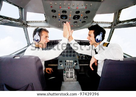 Pilots giving a high-five in an airplane cabin - stock photo