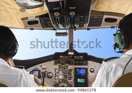 Pilots in the plane cockpit and blue sky - stock photo