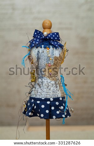 Pin cushion and pins as a figure of a woman in a dress - stock photo