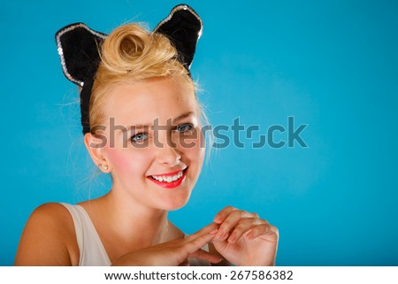 Pin up and retro style. Young smiling woman with black ears on head on blue background. Studio shot. - stock photo