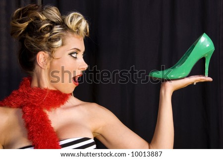 Pin-up girl holding green stiletto. - stock photo