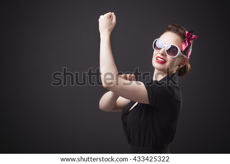 Pin-up girl in a classic gesture (  We Can Do It  ) - stock photo