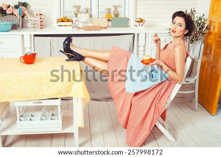 Pin-up girl style. Girl sitting in the kitchen to put his feet on the table, hands holding a muffin. - stock photo