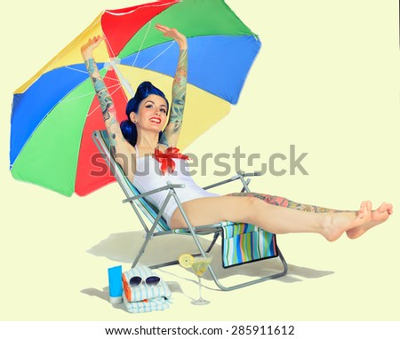 Pin-up girl tattoos happy resting on the beach stretching in the beach chair - stock photo