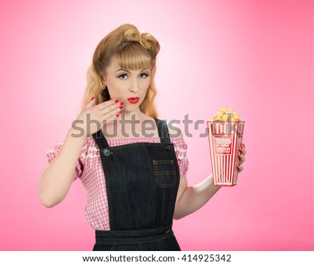 Pin up girl with carton on popcorn on a bright pink background - stock photo