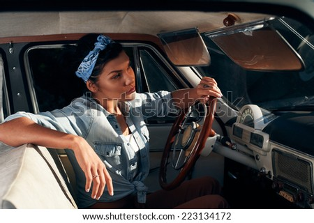 pin-up lady with tattoos wearing shirt in retro car - stock photo