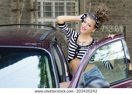 Pin up model poses in front of the car