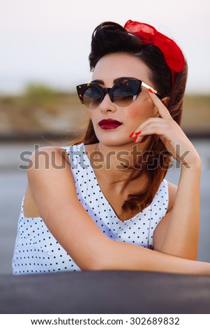 Pin-up poses with vintage sunglasses  - stock photo