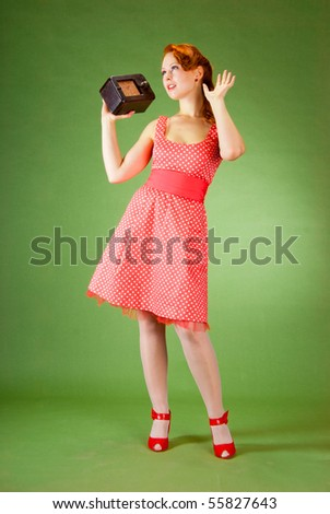 Pin-up style girl listening old radio - stock photo