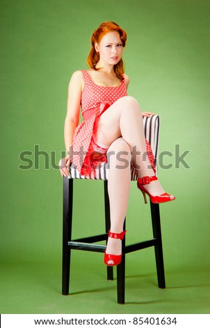Pin-up style girl sitting on the chair - stock photo