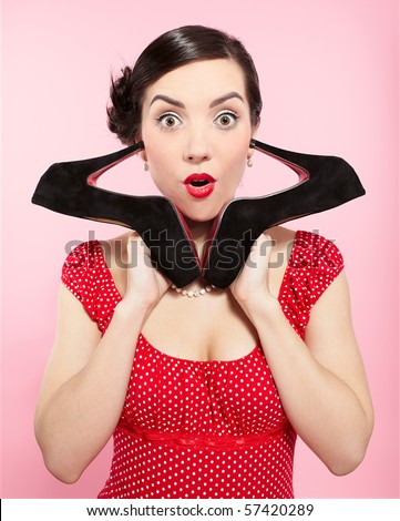 pin-up style portrait of beautiful brunette girl posing with court shoes - stock photo