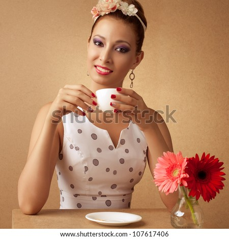 pin-up style portrait of beautiful brunette girl with tea cup near wooden table with red and pink herberas - stock photo