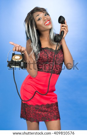 Pin up style with African Caribbean girl holding vintage telephone - stock photo