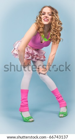 Pin-up woman in colorful clothes standing on the blue background - stock photo