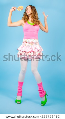 Pin-up woman with colorful lollipop smiling and dancing - stock photo
