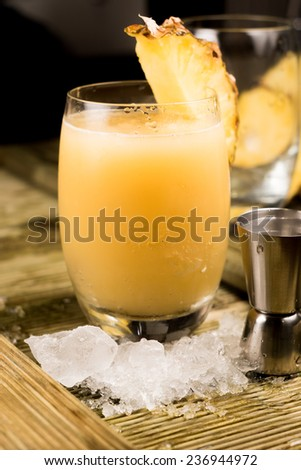 Pina colada cocktail next to a shot glass and ice - stock photo