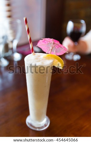 Pina colada in a tall glass with straw and umbrella served with a lemon slice