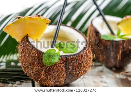 Pinacolada drink with mint served in a fresh coconut - stock photo