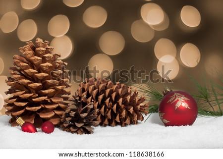 Pine cone and ornaments in snow with christmas lights background
