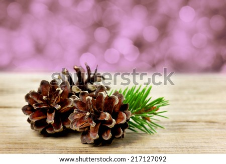 pine cones on a wooden board against christmas bokeh background, winter concept