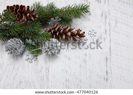 Pine cones with coniferous green branches and white christmas baubles