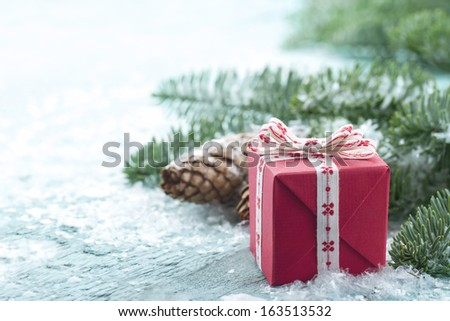 Pine cones, Xmas present and green spruce tree branches with snow in a decorative rustic Christmas setting on vintage light blue wooden background - stock photo