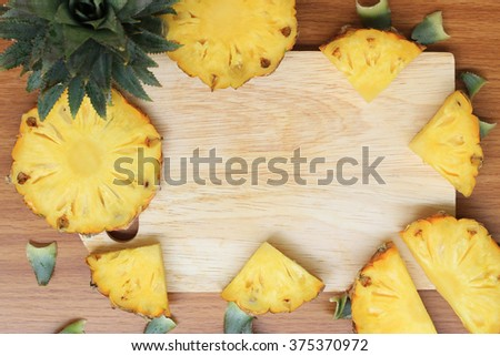 Pineapple and empty cutting board with space for your text - stock photo