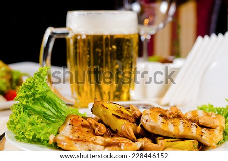Pineapple Cashew Chicken Dish with Mug of Beer Served in Restaurant - stock photo