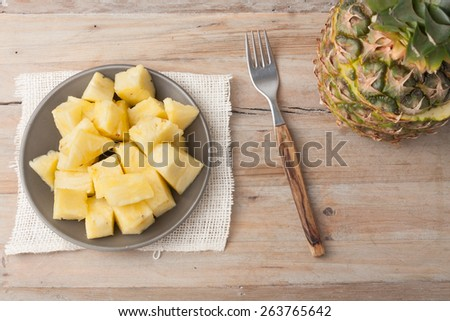 pineapple chunks on a plate on wooden rustic background - stock photo