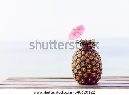 Pineapple fruit on wood table  by the beach background,retro filter effect