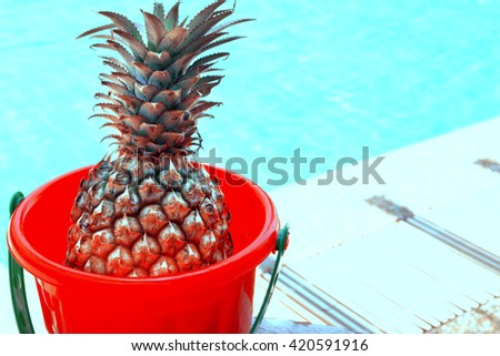 pineapple in toy bucket on wooden table. - stock photo