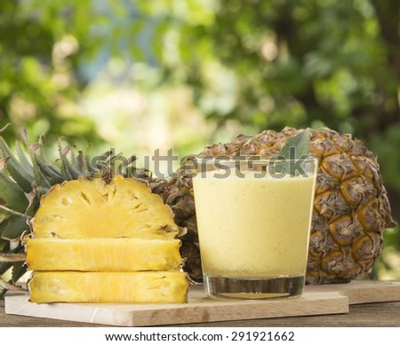 Pineapple juice and pineapple slice placed on a wooden table. - stock photo