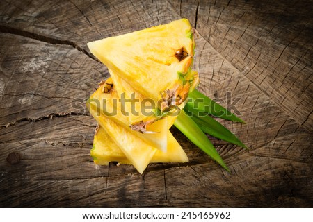 Pineapple. Slices isolated on wooden background. - stock photo